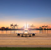 Cargo plane parking in airport runways and shipping port behind. Use for ship port logistic and air freight delivery service stock photography