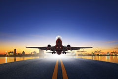 Cargo plane take off from airport runways against ship port back Stock Image