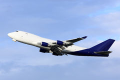 Cargo plane taking off. Big cargo airliner taking off into blue sky Royalty Free Stock Images