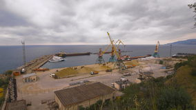 Cargo port. Crane with bucket makes loading sand into a truck. Shot at Sony camera in 4K stock video