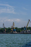 Cargo port. With cargo cranes on a blue sky background Stock Photo