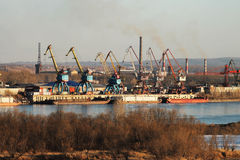 Cargo port on the river. Cranes, containers, barges in a cargo port on the river Royalty Free Stock Photo