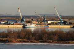Cargo port on the river. Cranes, containers, barges in a cargo port on the river Royalty Free Stock Images