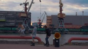 Cargo port at seafront. Cranes. Containers. Men on rollers skaters jump on pipe stock video