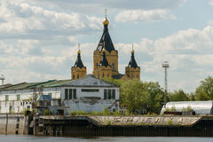 Cargo river port and Alexander Nevsky Cathedral on the Strelka. Nizhny Novgorod. Alexander Nevsky Cathedral in Nizhny Novgorod behind the buildings of the cargo Royalty Free Stock Photos