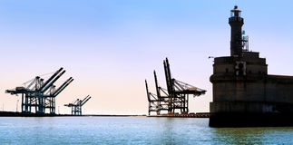 Cargo sea port. Old lighthouse. Sea cargo cranes. Royalty Free Stock Images
