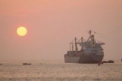 Cargo ship. And tugboats at sunset stock images