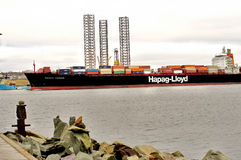Cargo  ship. Hapag lloyd commercial  ocean vessel  container ship sailing into port halifax harbor waterfront . sea cargo storage  and oil derrick Halifax nova Royalty Free Stock Photography