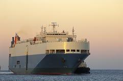 Cargo ship. LArge cargo ship with tug boat alongside, entering port Stock Photography