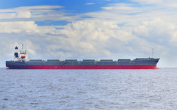 Cargo ship. In open sea under cloudy blue sky Stock Images