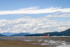 Cargo ship anchored in bay at low tide Stock Photo