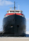 Cargo ship anchored at dock. A huge cargo ship is anchored at the dock in a frozen lake, front view Royalty Free Stock Photos