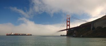 Cargo ship approaching Golden. Cargo ship with containers stacked high on deck approaches Golden Gate Bridge while fog is blowing into San Francisco Bay Royalty Free Stock Image