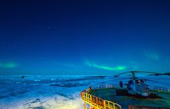 Cargo ship arrives in port for unloading on an ice floe.Bright colorful northern lights in the night sky. stock photos