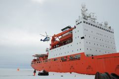 Cargo ship arrives in port for unloading on an ice floe. stock images