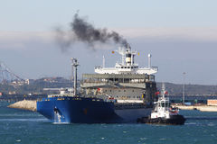 Cargo ship arriving at port, with smoke Stock Photography