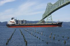 A cargo ship & the Astoria bridge. A cargo ship passing through the Astoria bridge Royalty Free Stock Image