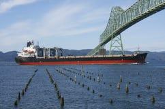 A cargo ship & the Astoria bridge. Royalty Free Stock Image