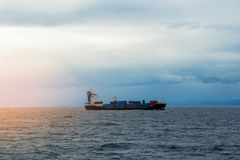 Cargo ship barge with containers on the sea horizon. At sunset stock photos