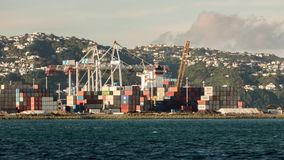 Cargo ship being loaded time lapse. At sunset in wellington city stock video footage