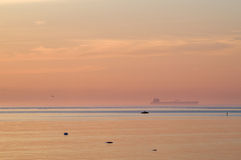Cargo ship in blue water haze after sunset Royalty Free Stock Photos