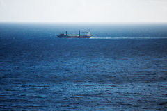 Cargo ship carries swims across the ocean Royalty Free Stock Images