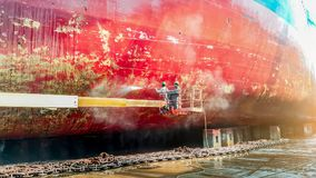 Cargo ship cleaning. Work in floating dry dock with water jet cleans the shipboard and have movement of people of the ship from sea vegetation before sandblast Stock Photography