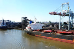 Cargo Ship at Coal Refinery. A cargo shipped docked on a harbor near a coal refinery Stock Images