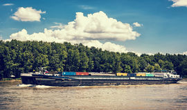 Cargo ship with containers on the Danube river, blue retro photo. Cargo ship with containers on the Danube river, Slovak republic. Goods transport. Blue retro Royalty Free Stock Photos