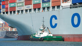 Cargo Ship COSCO EXCELLENCE departing the Port of Oakland. Oakland, CA - September 13, 2016: Tugboat PACIFIC STAR at the stern of Cargo Ship COSCO EXCELLENCE Stock Image
