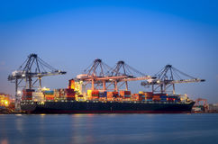Cargo ship and crane at port reflect on river, twilight time Royalty Free Stock Photo