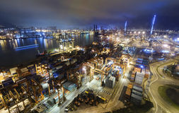 Cargo ship and crane at port reflect on sea bay, Royalty Free Stock Photos