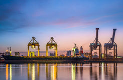 Cargo ship and crane at port reflect with water, twilight time. Stock Photos