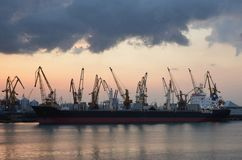 Cargo ship and cranes in the port, reflected in the water, twili stock image