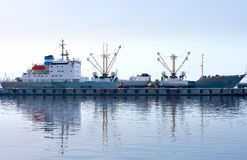 Cargo ship docked and loading in port fully. Reflected in water Royalty Free Stock Image