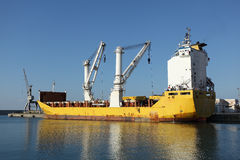 Cargo Ship Docked in Port. A yellow cargo ship docked in a port loading containers. Located into the industrial port of Imperia Oneglia (Liguria, Italy), a royalty free stock photo