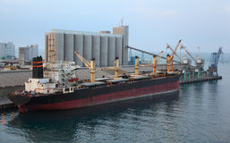 Cargo ship docked to industrial port Stock Image