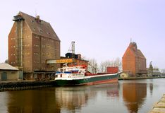 Cargo ship docked at warehouse. A view of a cargo ship docked beside a commercial warehouse along a canal or waterway in Darlowo, Poland Royalty Free Stock Photos