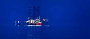 Cargo ship at dusk. A cargo ship loaded with a jack-up rig Royalty Free Stock Photos