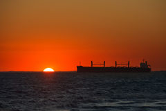 Cargo ship floats on the ocean at sunset time Royalty Free Stock Image