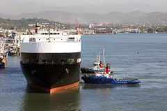 Cargo ship full of cars being pushed to dock. Ready to be offloaded Royalty Free Stock Photography