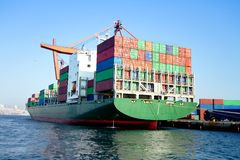 Cargo ship full of containers. Green cargo ship in port, fully loaded with containers royalty free stock image