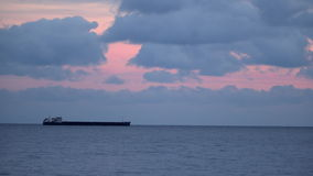 Cargo ship on the horizon. Evening sky with clouds.  stock video footage