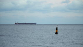 Cargo ship on the horizon line. Evening time. In the foreground you can see a buoy stock footage