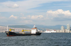 Cargo ship on Izmir background. Cargo ship at Izmir's bay and liner on background Stock Photo