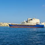 Ship leaves the harbor. Cargo ship leaves the harbor of Valletta Royalty Free Stock Photo