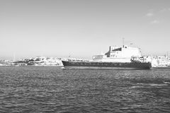 Ship leaves the harbor. Cargo ship leaves the harbor of Valletta. Black and white picture Royalty Free Stock Image