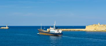 Cargo ship leaves the harbor. Of Valletta. Lighthouses indicate the entrance to the ports of Malta Royalty Free Stock Photography