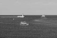 Cargo ship and pleasure craft. Cargo ship leaves the harbor of Valletta. Lighthouses indicate the entrance to the ports of Malta. Pleasure craft in the bay basin Royalty Free Stock Images