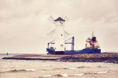 Cargo ship leaves the port of Swinoujscie, Poland. Cargo ship leaves the port of Swinoujscie in Poland, color toned picture Stock Photo